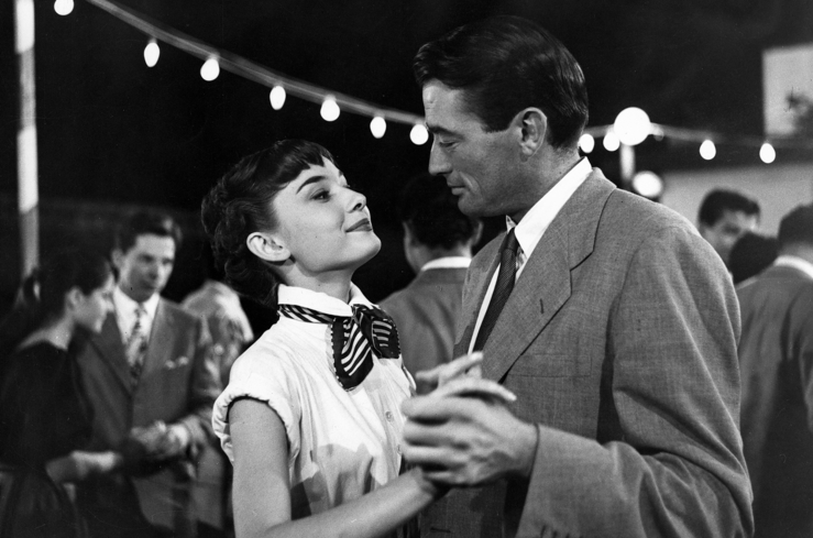 Audrey Hepburn and Gregory Peck star in Roman Holiday.