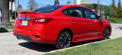 A three-quarter rear view of a 2016 Nissan Sentra SR compact sedan