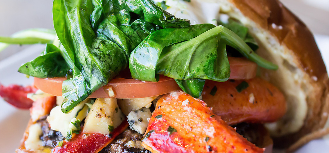 Spare Tire Kitchen & Tavern serves a decadent surf & turf burger topped with juicy lobster
