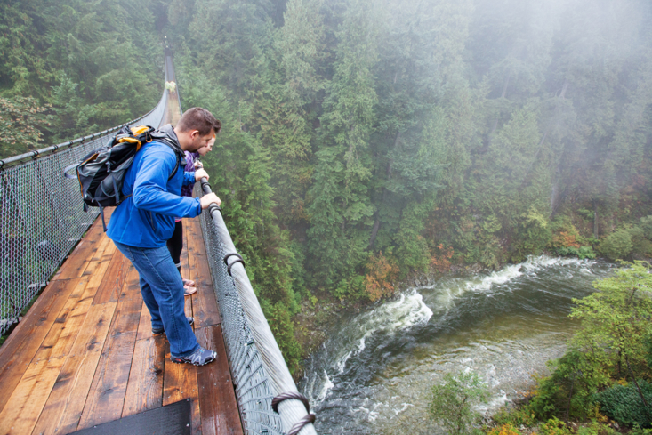 Visitors look down at the forest below Capilano Suspension Bridge in Vancouver