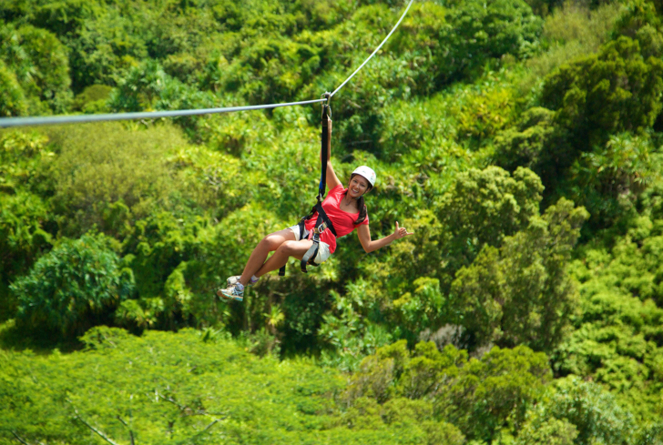 Zip line through Kauai's lush forests with Skyline Eco Adventures