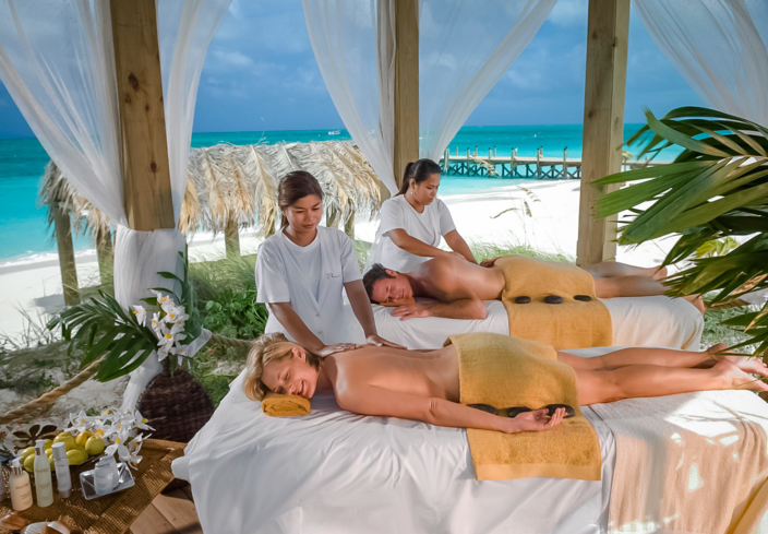 A couples massage in a tropical setting at Red Lane Spa at Beaches Turks & Caicos